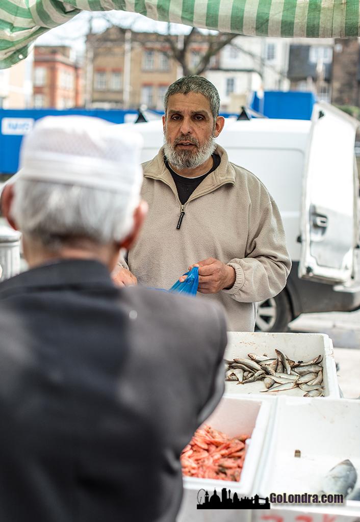 Tower Hamlets ilçesinde yer alan Whitechapel Market'de bulunan bir balıkçı ve müşterisi.